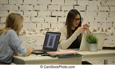 Two girls sit in the office and talking