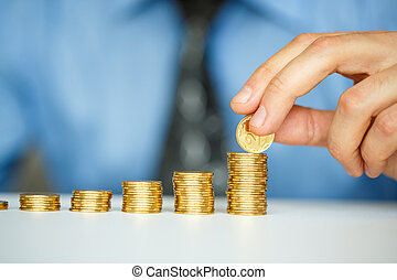 Male hand stacking gold coins into increasing columns -...