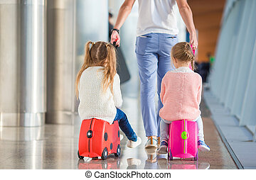 Adorable little girls with father in airport sitting on suitcase waiting for boarding