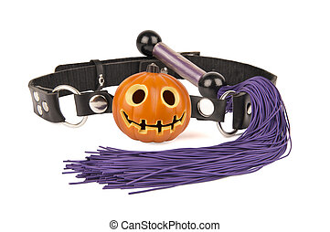 Pumpkin head ball gag and whip isolated on white background