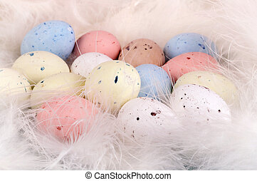Eggs and feathers - Soft pastel colored easter eggs on a bed...