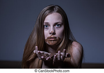 Bulimic girl eating chocolate