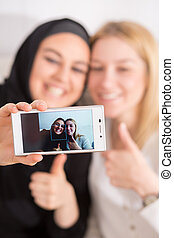 Friends taking selfie - Smiling muslim and european female...