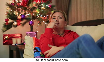 Woman sitting near the xmas tree - Depressive woman lying on...