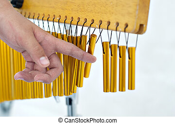 Playing with chimes - Hand playing one set of bar chimes on...