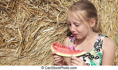Girl eat watermelon near the haystack - Young happy girl...