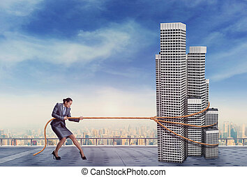 Businesswoman pulls a building - Businesswoman pulls a high...