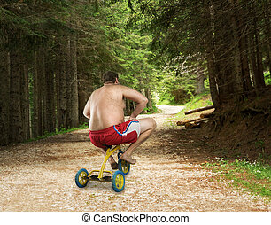 Adult naked man cycling on child's bicycle