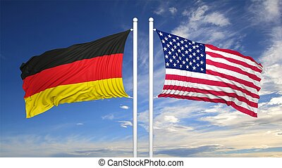 German and American flags against of blue sky