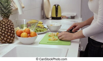 Closeup of woman hands slicing lime tangerine - Girl cut...