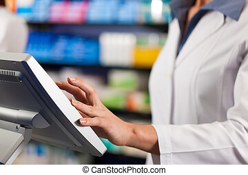 Female pharmacist at the cashier in pharmacy - Female...