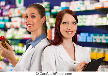 Pharmacist with assistant in pharmacy - Pharmacist with...