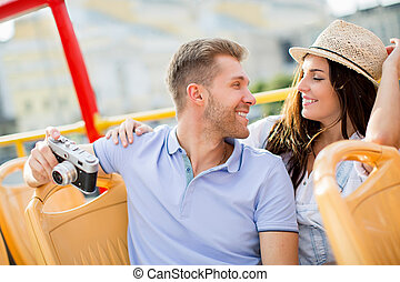 Smiling couple - Young people with a camera in the tour bus