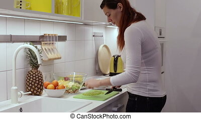 Pregnant woman cutting grape in the kitchen