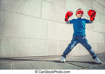 Concepts - Little boy with boxing gloves outdoors
