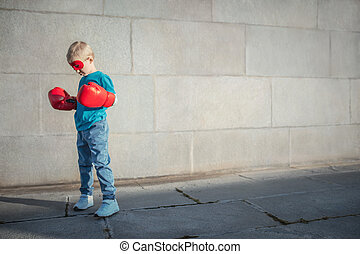 Strength - Little boy with boxing gloves outdoors