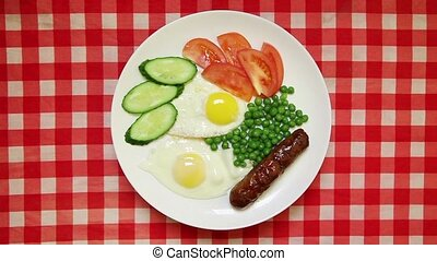 Fried eggs with sausage, peas and fresh vegetables on red...