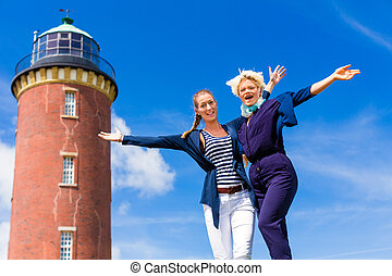 Friends standing at lighthouse on ocean - Woman enjoying...