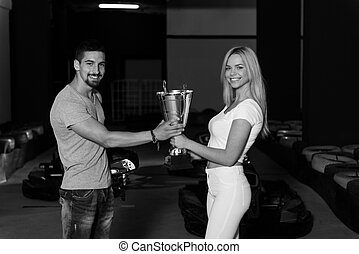 Woman Gives Man A Cup Speed Karting Race - Young Woman Gives...
