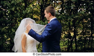 Groom lifts veil and kisses bride shot in slow motion close...