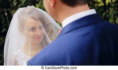 Groom lifting veil off beaming brides face on their wedding...