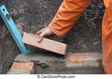 bricklaying - master puts a brick in cement mortar