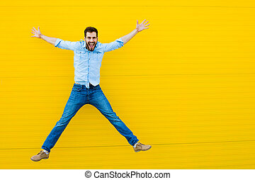 men jumping on yellow background - handsome man casual...