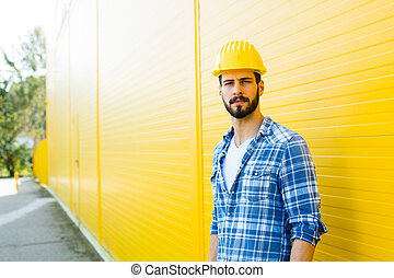 adult worker with helmet on yellow wall - worker with helmet...