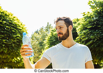 adult man drinking water from a bottle outside - close up of...