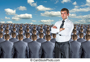 Confident businessman against crowd of business people