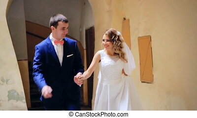 wedding day, couple running cheering in ancient city shot in...