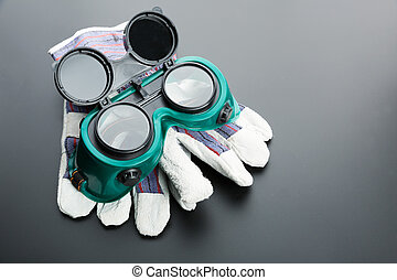Work gloves and protective glasses on grey