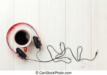 Headphones and coffee cup on wooden desk table. Music...