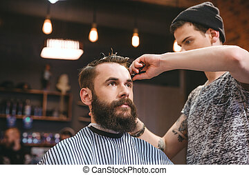 Skillful barber cutting hair of young man with beard -...