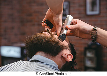 Young bearded man during beard grooming in barber shop -...
