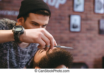 Young consentrated barber grooming beard of man with...