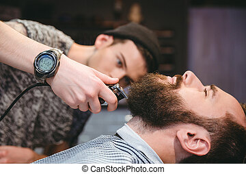 Bearded man getting his beard shaved by modern barber -...