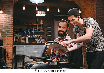 Happy barber and content client looking through magazine -...