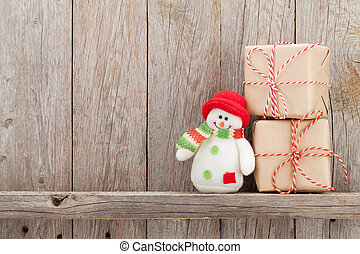 Christmas gift boxes and snowman toy in front of wooden wall...