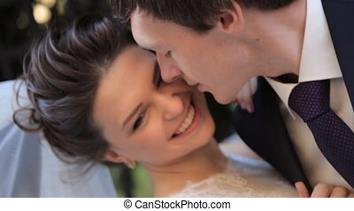Beautiful young couple bride and groom in a wedding dress in the sun tenderly looking at each other kissing happy family, loveshot in slow motion  close up