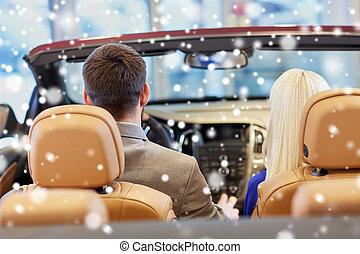 couple sitting in cabrio car at auto show - auto business,...