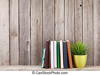 Wooden shelf with books in front of wooden wall View with...