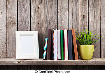 Wooden shelf with photo frames, books and plant in front of...