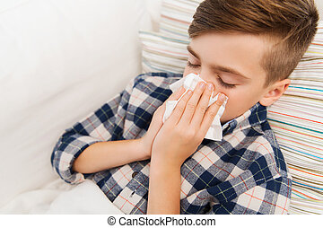 ill boy lying in bed and blowing his nose at home -...