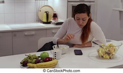 Girl sits at table with phone eating fruit salad - Girl eats...