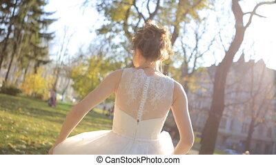 Beautiful young bride in white wedding dress spinning around...
