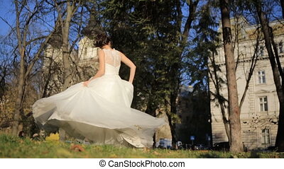 young beautiful bride standing in park and sways her dress...