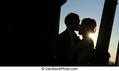 Newly wed couple watch sunset shot in slow motion close up -...