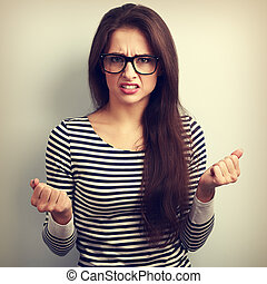Nervous angry young woman in glasses with aggressive...