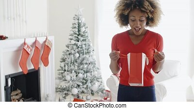 Happy young woman opening Christmas gifts